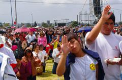 QUITO, ECUADOR - JULY 7, 2015: People raising the hand to receive blessings - stock photo
