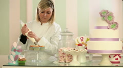 Young pastry chef with pastry bag is garnishing cup cakes Stock Footage
