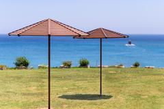 Beach umbrella on green grass at the sea in Cyprus, a boat at the horizon - stock photo