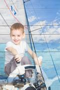 Double exposure a little boy at the helm and yacht - stock photo