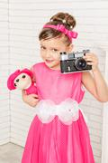little girl with plush toy and vintage camera - stock photo