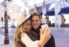 Young couple taking smartphone selfie at xmas on New Bond street, London, UK - stock photo