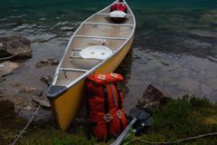 Orange colour backpack leaning against yellow canoe, Moraine lake, Banff Stock Photos
