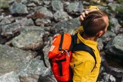 High angle view of mid adult man carrying orange colour backpack, Moraine lake, Stock Photos
