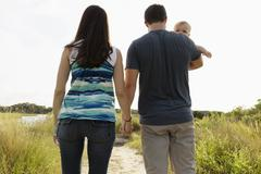 Rear view of mid adult parents carrying baby daughter on riverside stroll Stock Photos