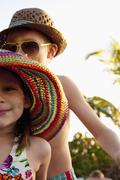 Cropped portrait of girl and brother wearing sunhats on beach, Sanibel, Florida, - stock photo
