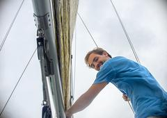 Low angle view of young man holding onto sailboat mast looking at camera smiling Stock Photos