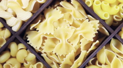 Assorted different kinds of pasta in a wooden box - stock footage