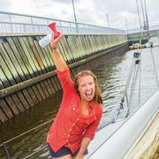 Young woman on sailboat in marina arm raised holding air horn, looking at camera - stock photo