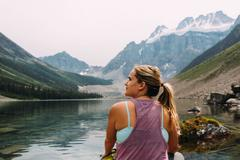 Rear view of mid adult woman sitting at waters edge looking away, Moraine Lake, - stock photo