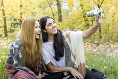 Young women taking selfie in forest, Hampstead Heath, London - stock photo