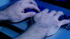 Man typing on laptop keyboard, blue toned Stock Footage