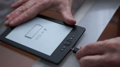 Amazon Kindle E-Reader with low battery icon, no logo visible charging - stock footage