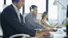 4K Happy workers in city office chatting & listening to music through headphones Stock Footage
