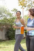 Young women out walking wearing sports clothing carrying water bottles laughing - stock photo