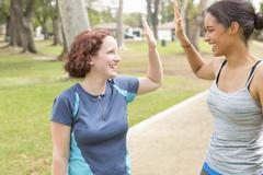 Young women wearing sports clothing face to face smiling doing high five - stock photo