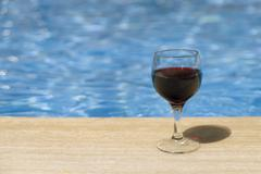 Full wine glass near the pools edge. Stock Photos