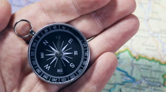 Hand holding a compass with swinging needle Stock Footage