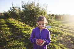 Girl in orchard holding apple looking down smiling Kuvituskuvat