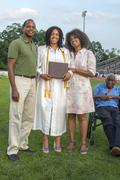 Teenage girl with parents and grandfather at graduation ceremony Stock Photos