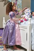 Side view of girl dressed up as princess play acting with teddy bear - stock photo