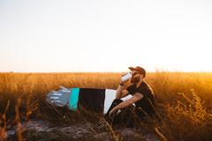 Male surfer drinking coffee in field of long grass at sunset, San Luis Obispo, - stock photo