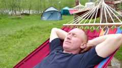 4K. Adult  Man shake in hammock against tourist tent Stock Footage