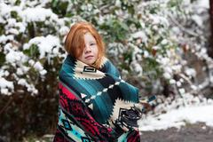 Red haired girl in front of snow covered trees, wrapped in aztec pattern blanket Stock Photos