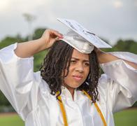Teenage girl adjusting cap at graduation ceremony Stock Photos