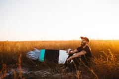 Male surfer drinking beer in field of long grass at sunset, San Luis Obispo, - stock photo
