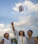 Teenage girl and sisters throwing her cap at graduation ceremony Stock Photos