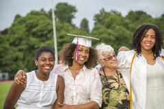 Teenage girl with sister and family at graduation ceremony - stock photo