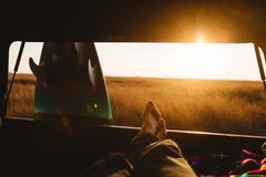 Male surfer with bare feet up in back of jeep at sunset, San Luis Obispo, - stock photo