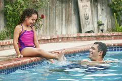 Girl wearing swimwear sitting poolside splashing father smiling Stock Photos