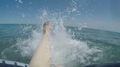 Female legs splashing water in the sea, slowmotion Stock Footage