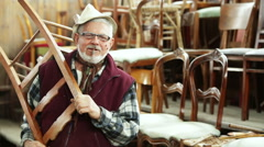 Senior secondhand dealer smoking cigar portrait in his shop - stock footage