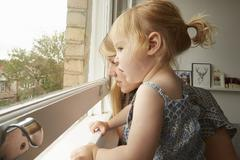 Mid adult woman and toddler daughter gazing out from living room window - stock photo