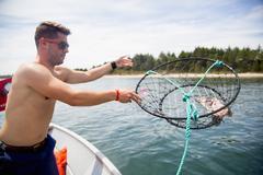 Mid adult man throwing baited crab trap from fishing boat, Nehalem Bay, Oregon, Kuvituskuvat