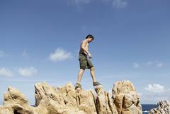 Low angle side view of young man climbing on rocks, Costa Paradiso, Sardinia, Stock Photos