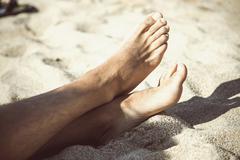 Cropped view of bare feet on sandy beach, Costa Paradiso, Sardinia, Italy - stock photo