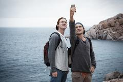 Young men in front of ocean using smartphone to take selfie smiling, Costa - stock photo