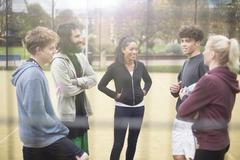 Group of adults standing on urban sports pitch, talking Stock Photos