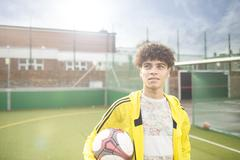 Portrait of young man holding football, on urban football pitch - stock photo