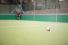 Young man on urban football pitch - stock photo