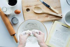 Overhead view of person blending butter with flour, making scones - stock photo