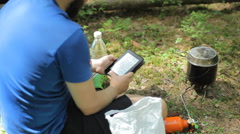 Man reads an e-book in the forest. Near the tourist pot on a gas burner Stock Footage