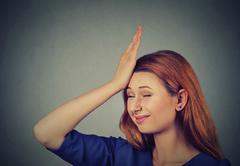 Regrets wrong doing. Silly young woman, slapping hand on head having duh - stock photo