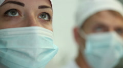Intern closely watching the progress of the operation on the monitor of doctor. Stock Footage