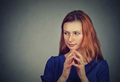 sneaky, sly, scheming young woman plotting something - stock photo
