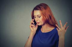 upset sad, unhappy, serious woman talking on phone displeased with conversati - stock photo